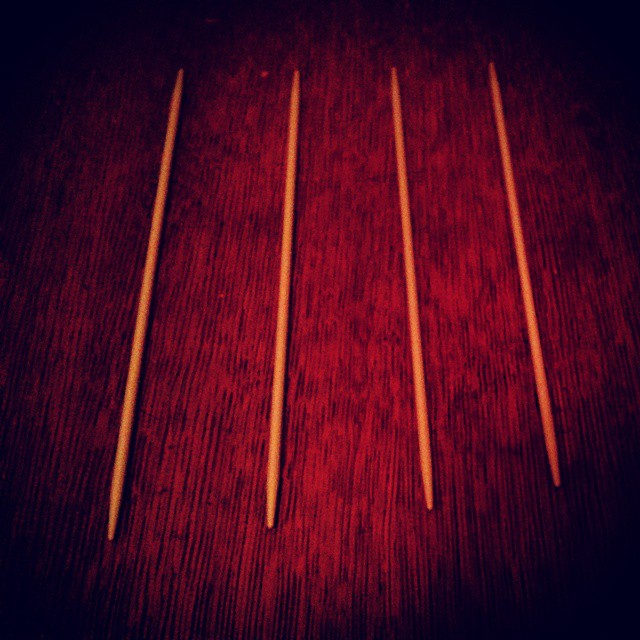 a photo of four double pointed bamboo knitting needles