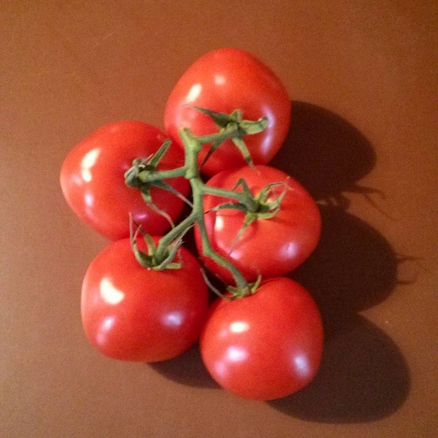 a photo of five tomatoes on the vine