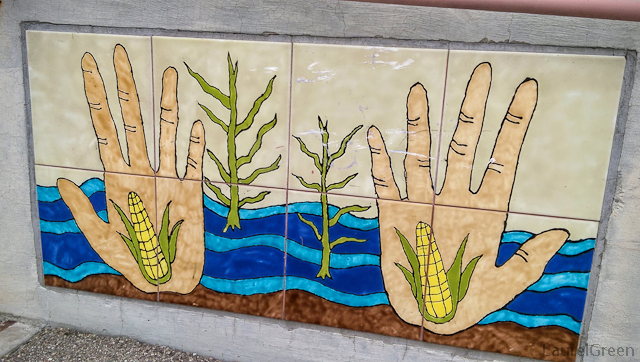 tile art of hands and corn