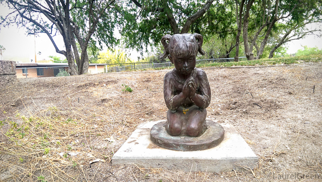 bronze statue of a little girl praying