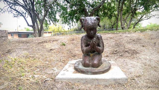 bronze statue of a little girl praying