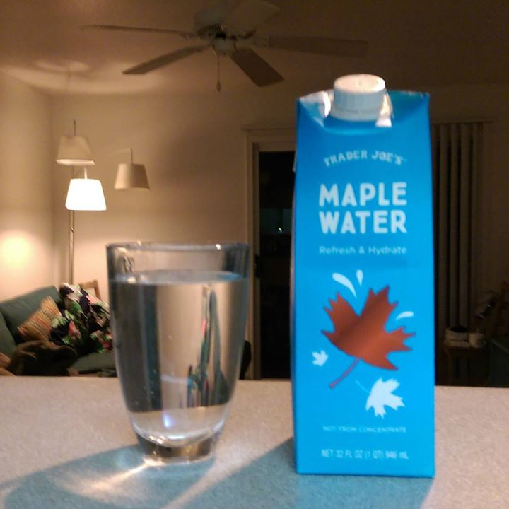 a photo of a glass of trader joe's maple water and the water carton