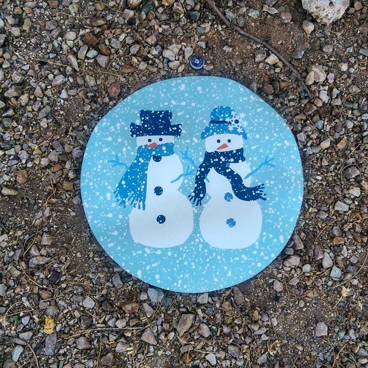 a photo of a placemat with with two snowmen lying in the desert