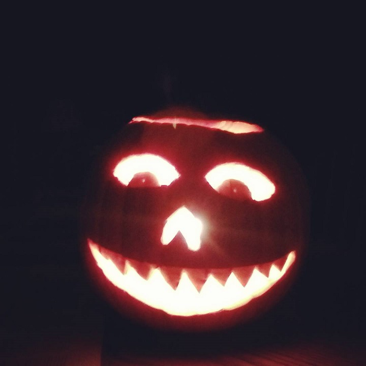 photo of a lit-up jack o' lantern in the dark