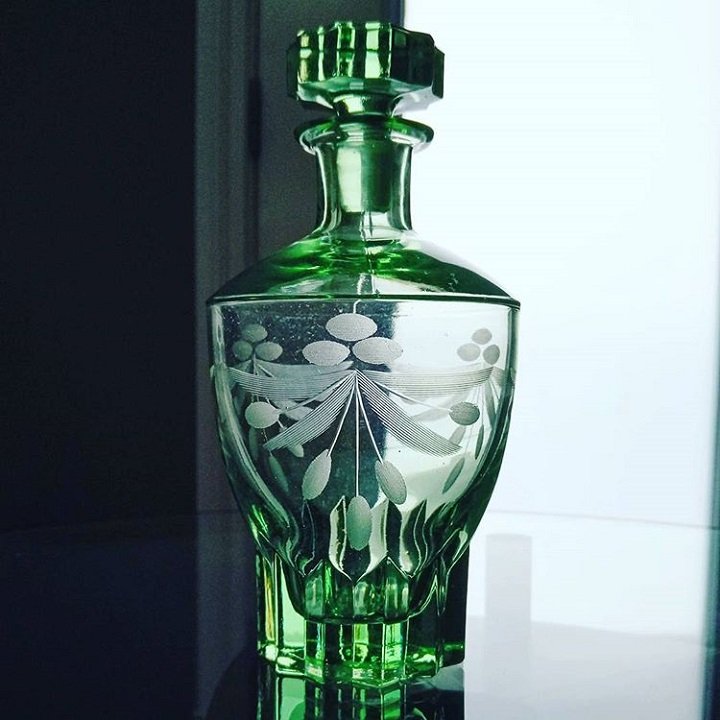a photo of a green glass decanter with a design etched into its surface