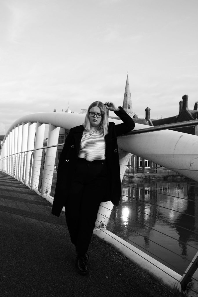 black and white image of a model leaning against a bridge railing. She is wearing black trousers, shoes and coat with a black and white striped top