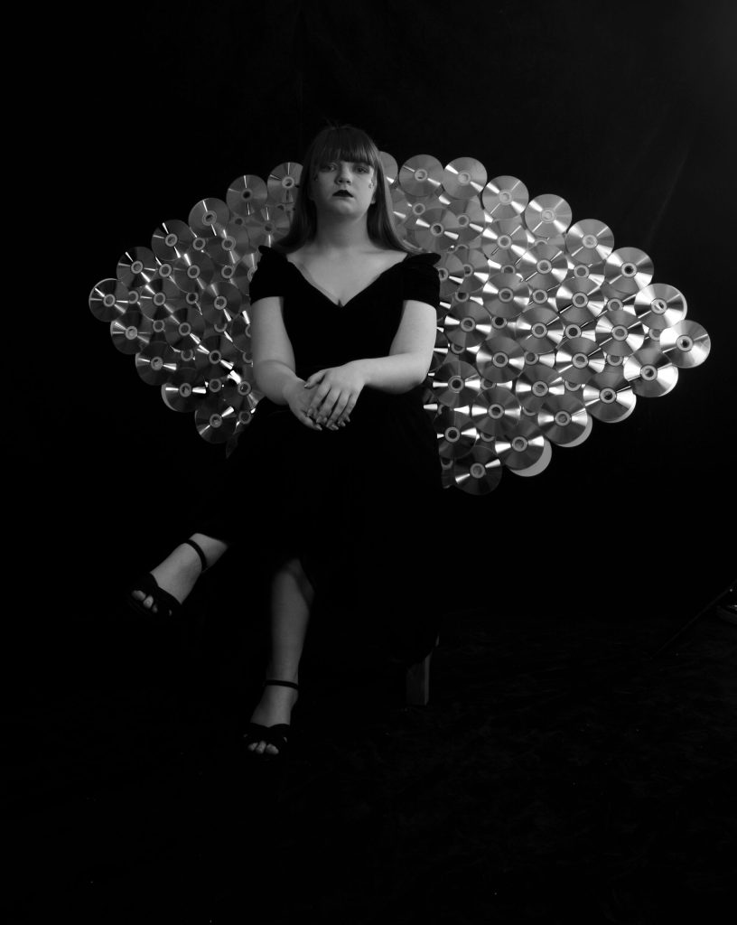 black and white image of model sat in front of a peacock tail made of CD's