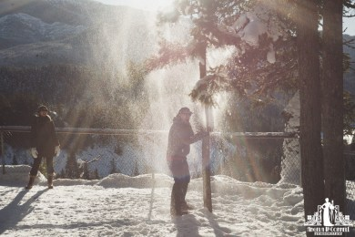 Natural light portrait of a man shaking snow off a tree with a laughing woman looking on