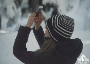 Natural light portrait of a young woman in the snow taking a photo on her iPhone of a snowy trees on Cypress Mountain in Vancouver