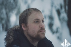 Natural light portrait of a bearded young man looking over a snow covered landscape