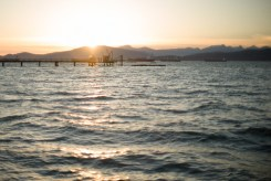 People on a pier with sunset and mountains in the background and waves in the foreground