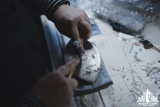 Photo of a jewellery designer hammering a new piece on a desk with drawn designs and works in progress