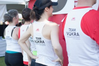 Group of people wearing Team VOKRA tank tops posing as a group before a fun run
