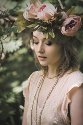 Natural light portrait of a young woman wearing a flower crown looking down