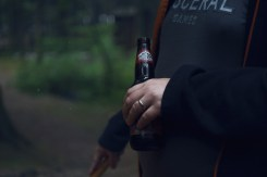 Image of a man drinking beer next to a campfire