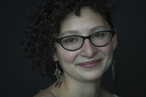 Natural light portrait of a young woman with glasses and curly hair smiling