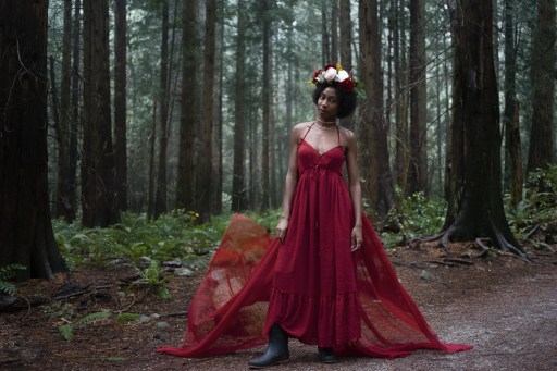 Natural light portrait of a young woman in a red dress and flower crown standing in the forest at Pacific Spirit National Park in Vancouver BC
