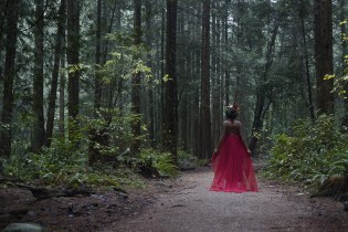 Natural light portrait of a young woman in a red dress and flower crown walking down a path in a forest in Pacific Spirit National Park in Vancouver BC