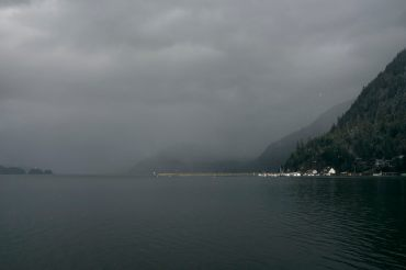 Moody image of sunlight hitting a marina and breakwater at Harrison Lake with cloud covered mountains in the background