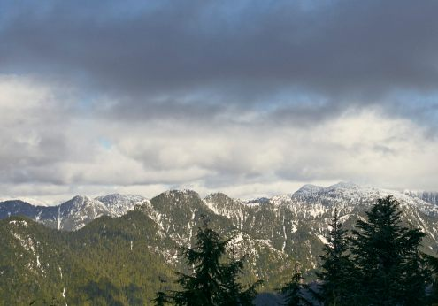 Image of partially snow covered mountain ranges on a partly cloudy day from the top of Dog Mountain