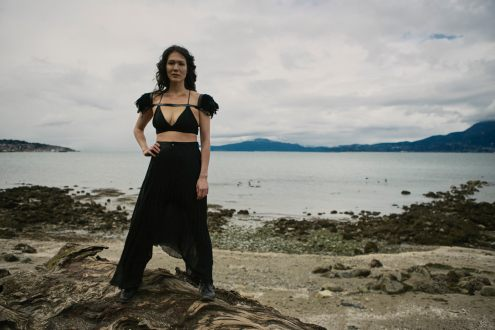 Outdoor natural light portrait of a woman on a rocky shoreline with a powerful stance looking straight at the camera