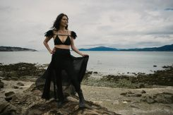 Outdoor natural light portrait of a woman on a rocky shoreline holding her long skirt as it catches the wind