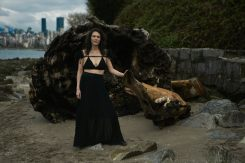 Outdoor natural light portrait of a woman posing in front of a large washed up log on a rocky shoreline