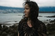 Outdoor natural light portrait of a woman standing on a rocky shoreline with moody skies looking out over the water while the wind blows her curls around her face