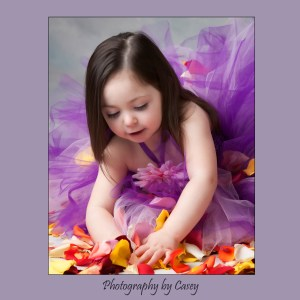 Photograph of little girl playing with rose petals