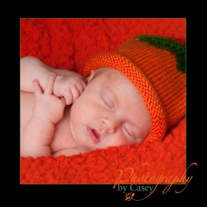 photography of sleeping newborn baby in pumpkin hat