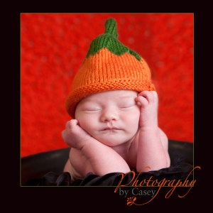 newborn sleeping baby with pumpkin hat photographer