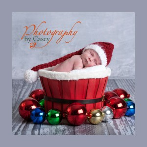 Photograph of Newborn in Christmas basket with Santa Hat