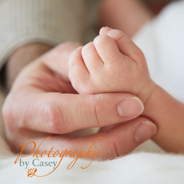 Newborn baby hand in Dad's