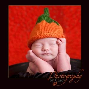 newborn sleeping baby with pumpkin hat photographer