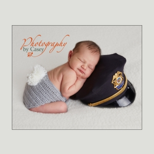 Newborn Baby posed with Dad's police hat