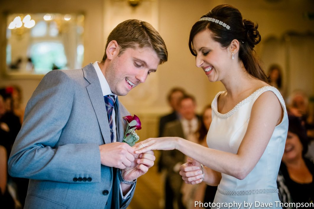 The groom places the ring on the brides finger.