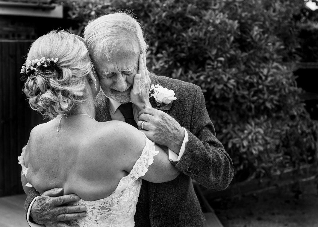 The father if the groom cries as he sees his daughter for the first time in her wedding dress.