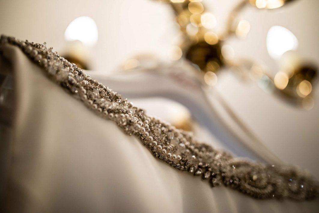 A wedding dress hangs from a light fitting.