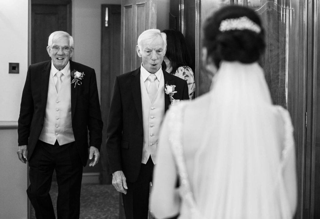 The bried's father and step father react as they see her in her dress
