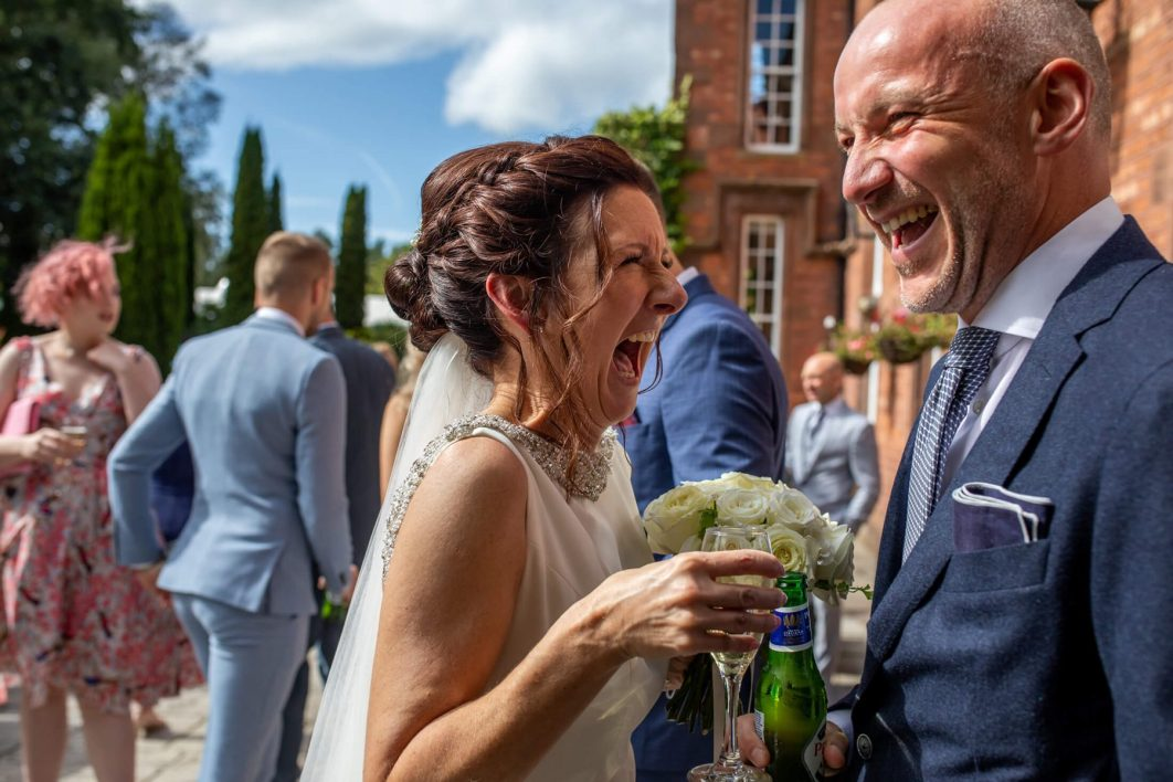 The bride laughs with her bother after her wedding.