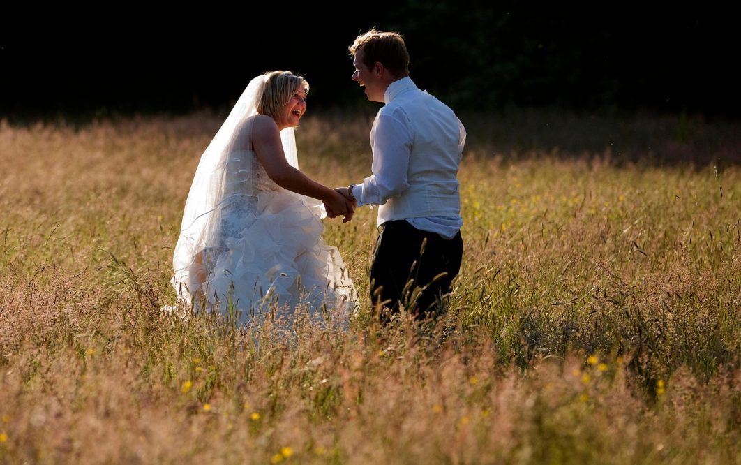 The bride and groom laugh in the long grass following their wedding at Iscoyd Park - Iscoyd Park Wedding Photographer