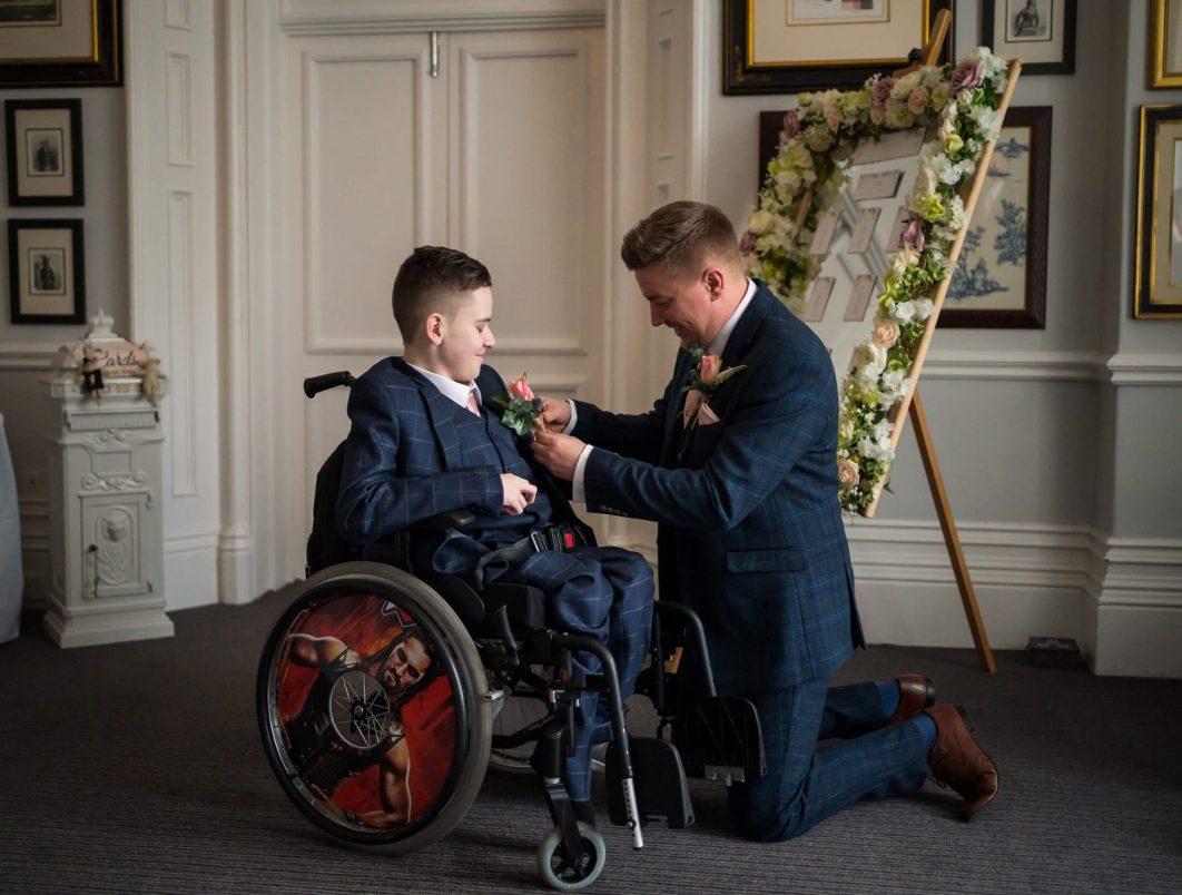 Hollin Hall Hotel Wedding Photographer - The groom pins a flower on the brides son