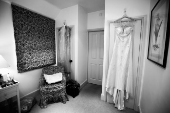 The bridal gown hangs from the door
