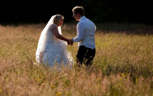 The bride and groom laugh in a field