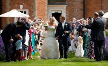 Guests shower the bride and groom with confetti