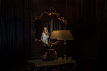A bride reflected in a mirror alongside a lamp