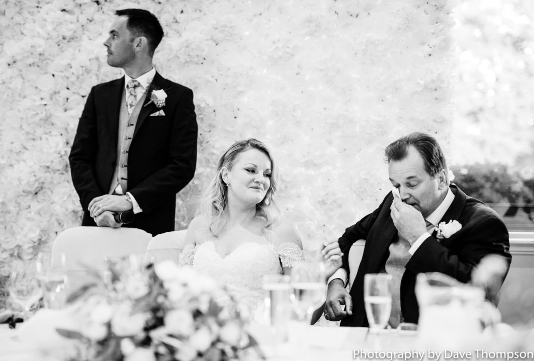 The bride smiles as her father cries
