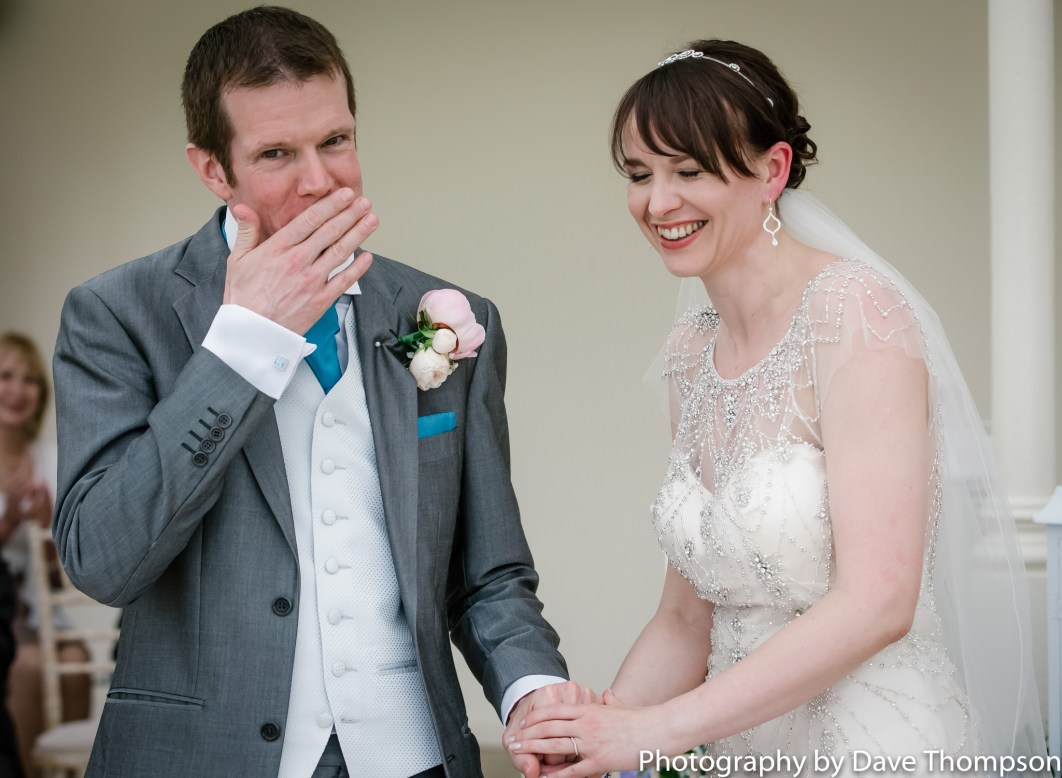 The groom wipes his lips after kissing the bride
