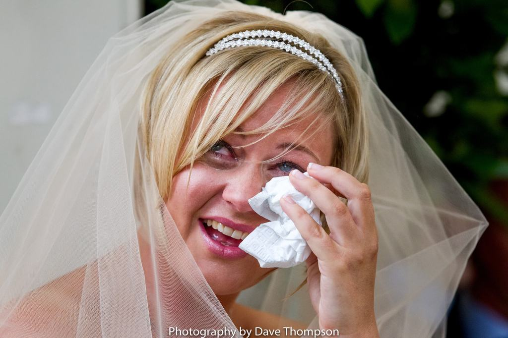 The bride wipes her eyes during her wedding