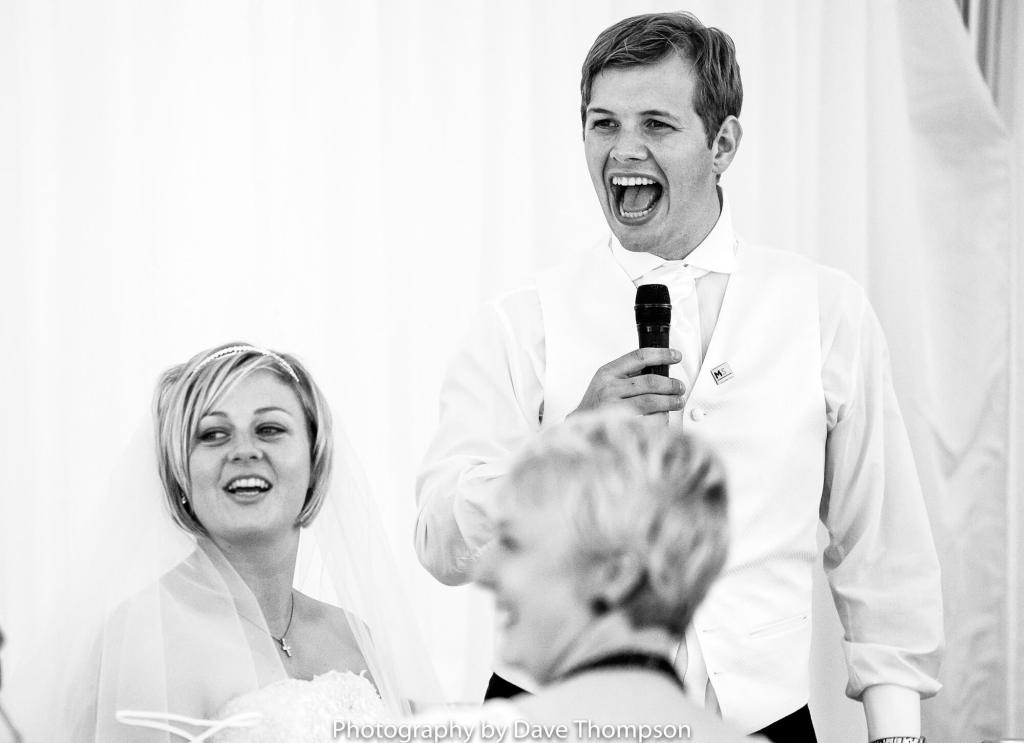 The groom laughs during his speech